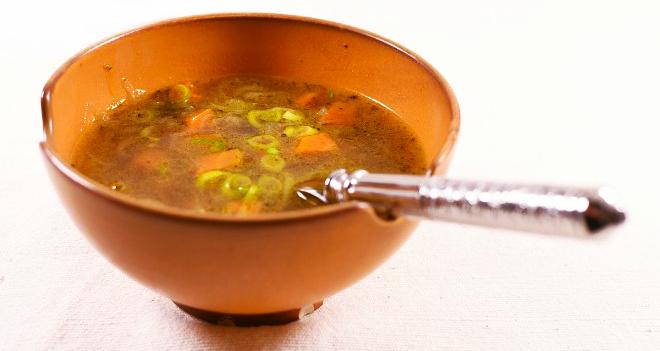"""Ribollita mit Olivenblätter in einer Suppenschale serviert. Diese leckere Resteverwertung wird, durch die Verwendung von Olivenblättern mit ihren würzigen Geschmack und gesundheitsfördernden Eigenschaften, in aussergewöhnlicher Weise """"aufgepimpt""""."""
