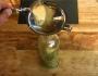 Nach dem Einfüllen der Olivenblätter in die Flasche wird Rohrzucker dazugegeben